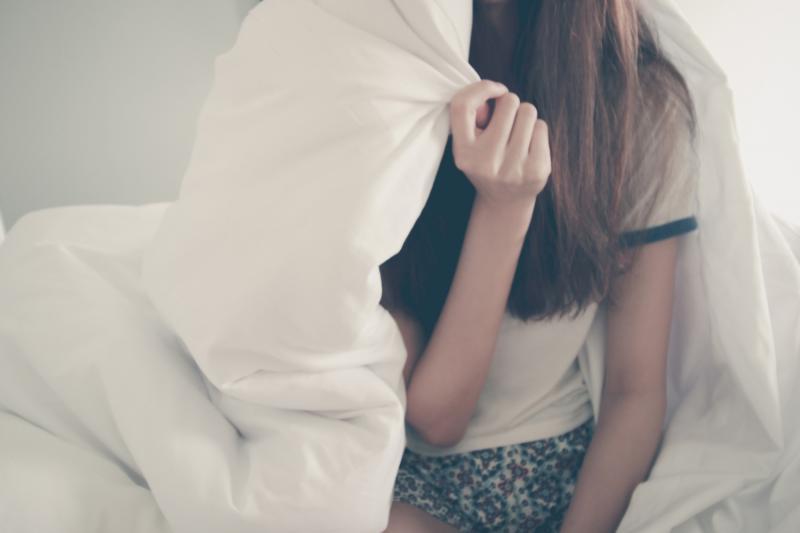 girl hiding under duvet