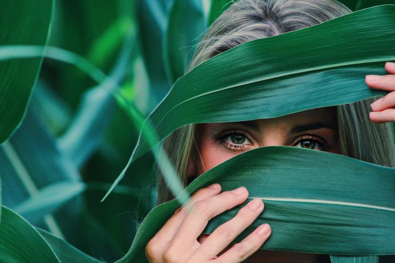 girl peering through plants