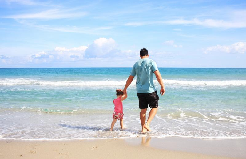 father and daughter in sea at beach