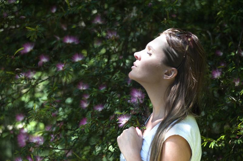 girl next to flowers breathing calm