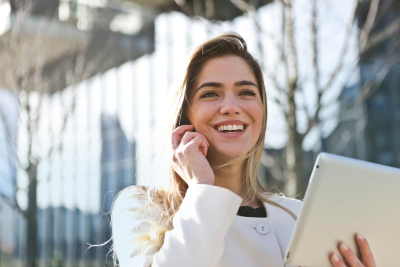 business woman smiling holding tablet outside