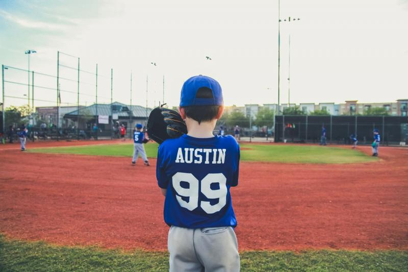 boy playing baseball with name on shirt