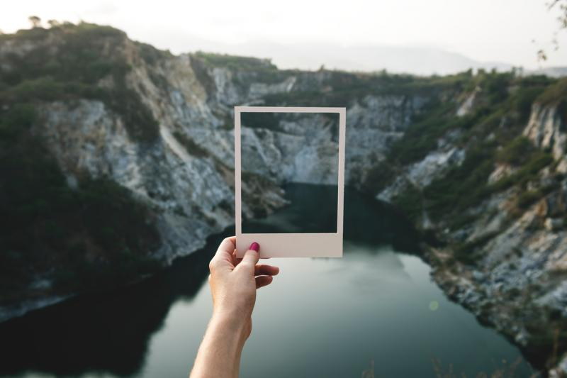 girl holding polaroid over river and hills